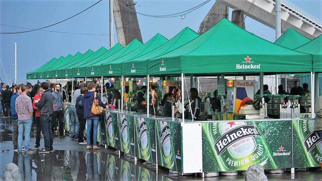 Green Heineken branded Folding Tent Bar in a row with green roofs and bespoke half height side walls and counters for serving drinks from.