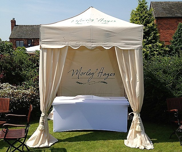 Royal Folding Tent – Ecru in colour with scalloped roof and elegant corner curtains in wedding garden setting