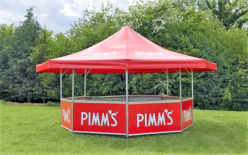 8-sided Pavilion kiosk with red roof and red base panels branded with the Pimms brand of drink