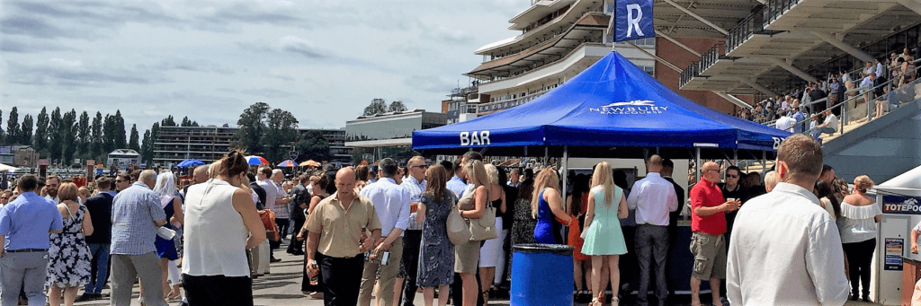 Blue 8-sided drinks bar situated at a racecourse sporting event serving drinks