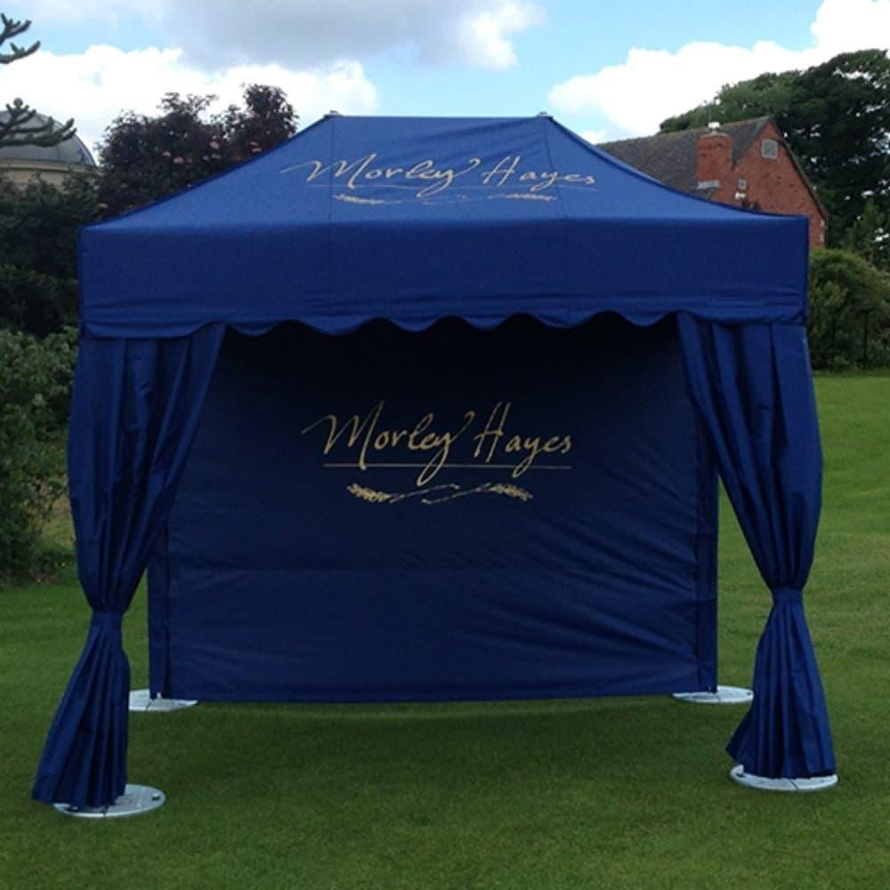 <p>Tent – Royal – Morley Hayes Golf Club</p> <p>3m x 2m</p> <p>Morley Hayes Golf Course have had beautiful tents made for their corporate hospitality events. Their choice is a Royal Tent with back wall and two front curtains. The tent roof, curtains and back wall has been produced in their own corporate blue colouring with their logo in gold. It makes a beautiful send off and a wonderful welcome back to the last hole. This is an excellent product for businesses who offer corporate hospitality products.</p>