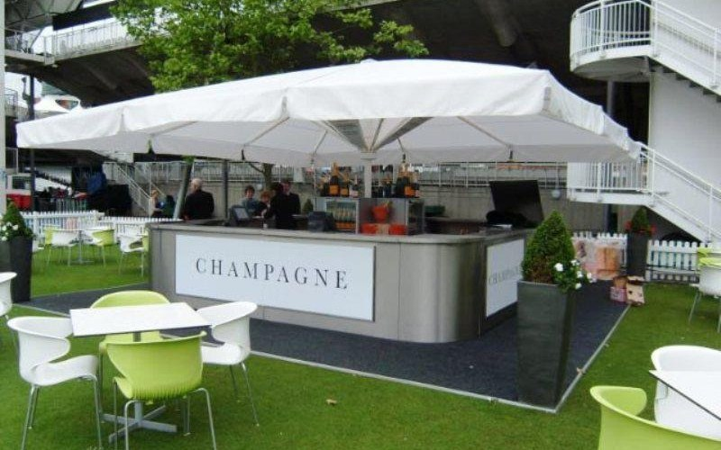A stainless-steel bespoke design outdoor champagne umbrella bar with bar counters, rounded corners, large umbrella in centre with refrigerators in the centre with room for personnel to serve premium champagne or other premium drinks at high profile sporting events and venues