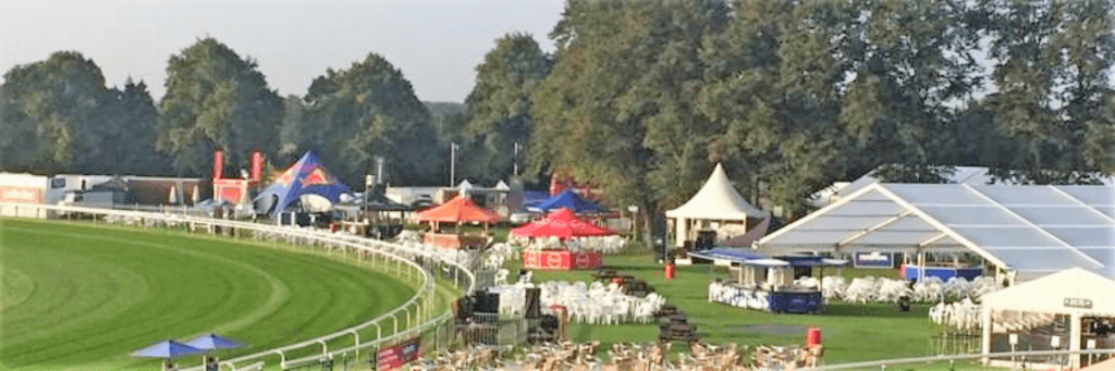 Panorama of a racecourse showing pavilion bars set up on champagne lawn for premium sports event