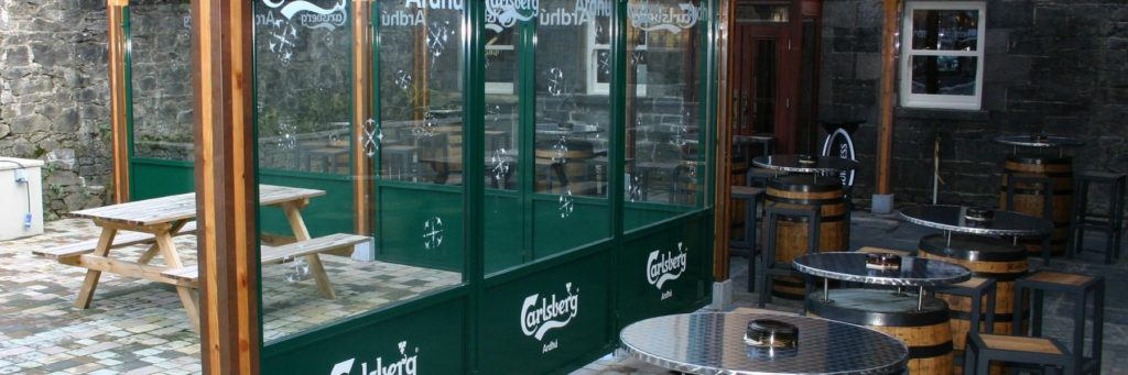 Outdoor Pub Beer Garden defined using Sirocco Pavement screen branded with Carlsberg and combined with wooden pergola to blend with the overall surrounds