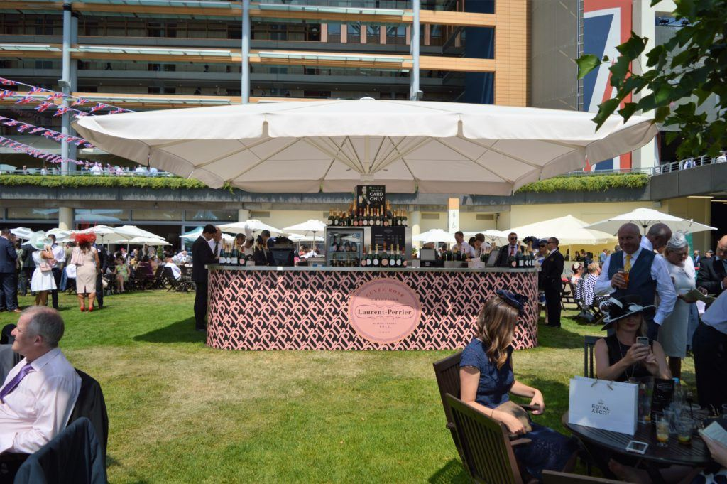 Premium Champagne Umbrella Bar with Laurent Perrier Branding and white umbrella shade on a VIP hospitality area at a high profile sporting event