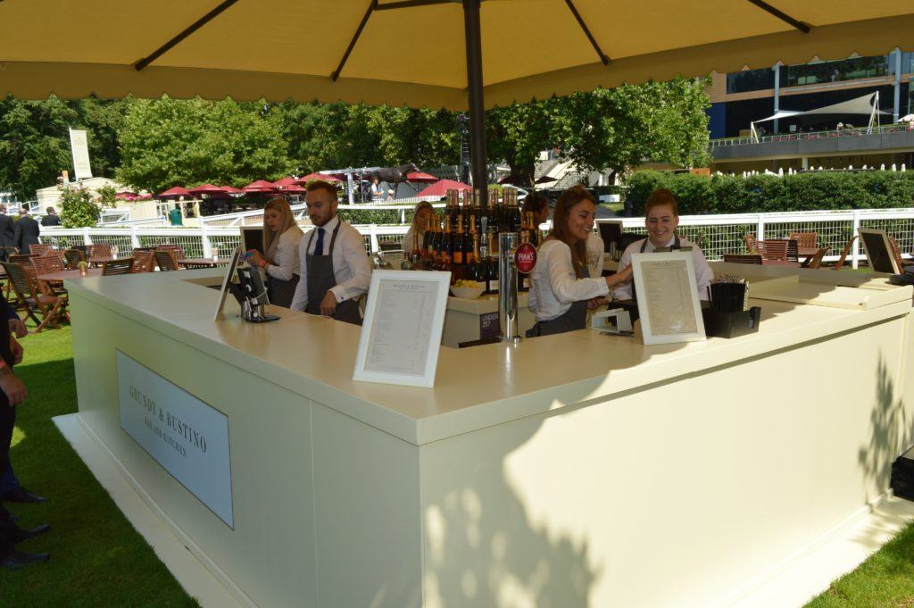 Close up shot of a bespoke wooden champagne umbrella event bar at Ascot Racecourse, showing the bar counters and umbrella shading operators from sun or rain.