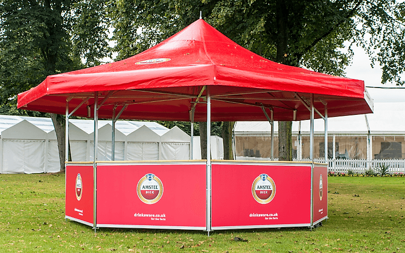 8-sided Event Kiosk with Red Amstel branded base panels and red Amstel roof cover