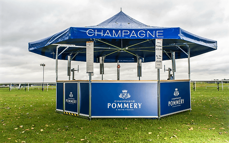 8 sided premium champagne bar branded blue for Pommery champagne set out at a racecourse venue