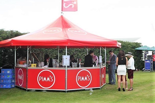 <p>Event, Mobile &amp; Stadia Bars &#8211; Tents &amp; Marquees &#8211; Octagonal Pavilion</p> <p>&nbsp;</p> <p>Pimm&#8217;s &#8211; Outdoor Racecourse Bar</p> <p>&nbsp;</p> <p>These type of bars are loved by many racecourses as they are spacious and draw the crowds giving them significant revenue  Fully branded printed base panels and printed roof.   A roof flag is also branded in matching colours and logo making the outdoor bar stand out in the crowd</p>
