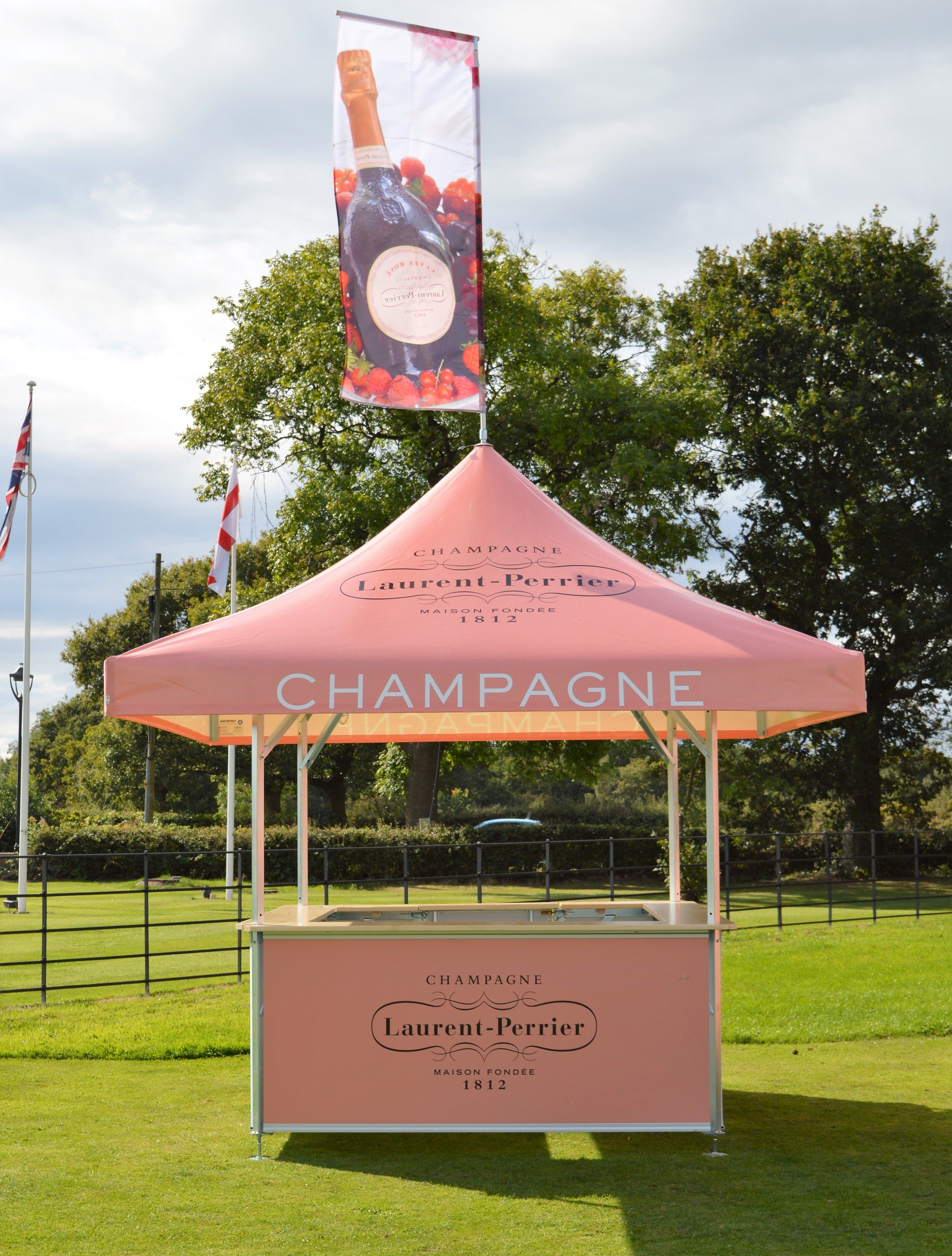 <p>Event, Mobile & Stadia Bars – Tents & Marquees – Square Pavilion.</p> <p> </p> <p>Laurent Perrier Champagne Bar with branded Roof Flag</p> <p> </p> <p>Square Pavilions are ideal for smaller areas when space is at a premium. Can be branded to suit customer requirements.</p> <p> </p> <p>Ideal for serving drinks from for example premium champagne brands, but also serve well as an information point, sampling stand, ticket collection point and many more versatile uses</p>