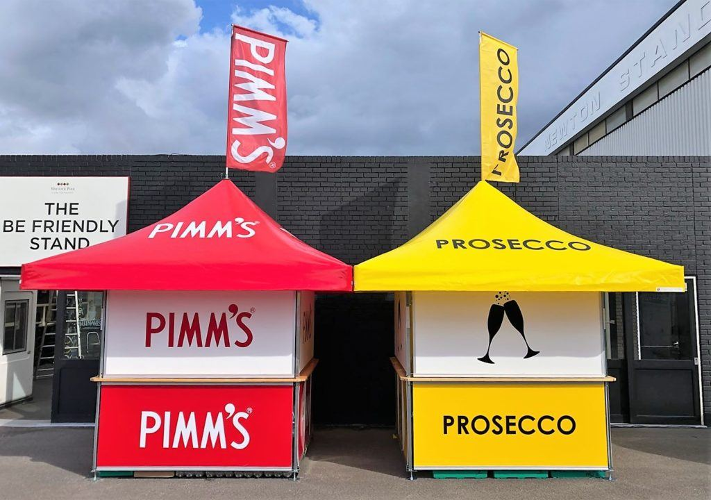 2 x 4-sided square pavilion kiosks branded as Pimm's and Prosecco outdoor event bars with both roof and base panels being branded