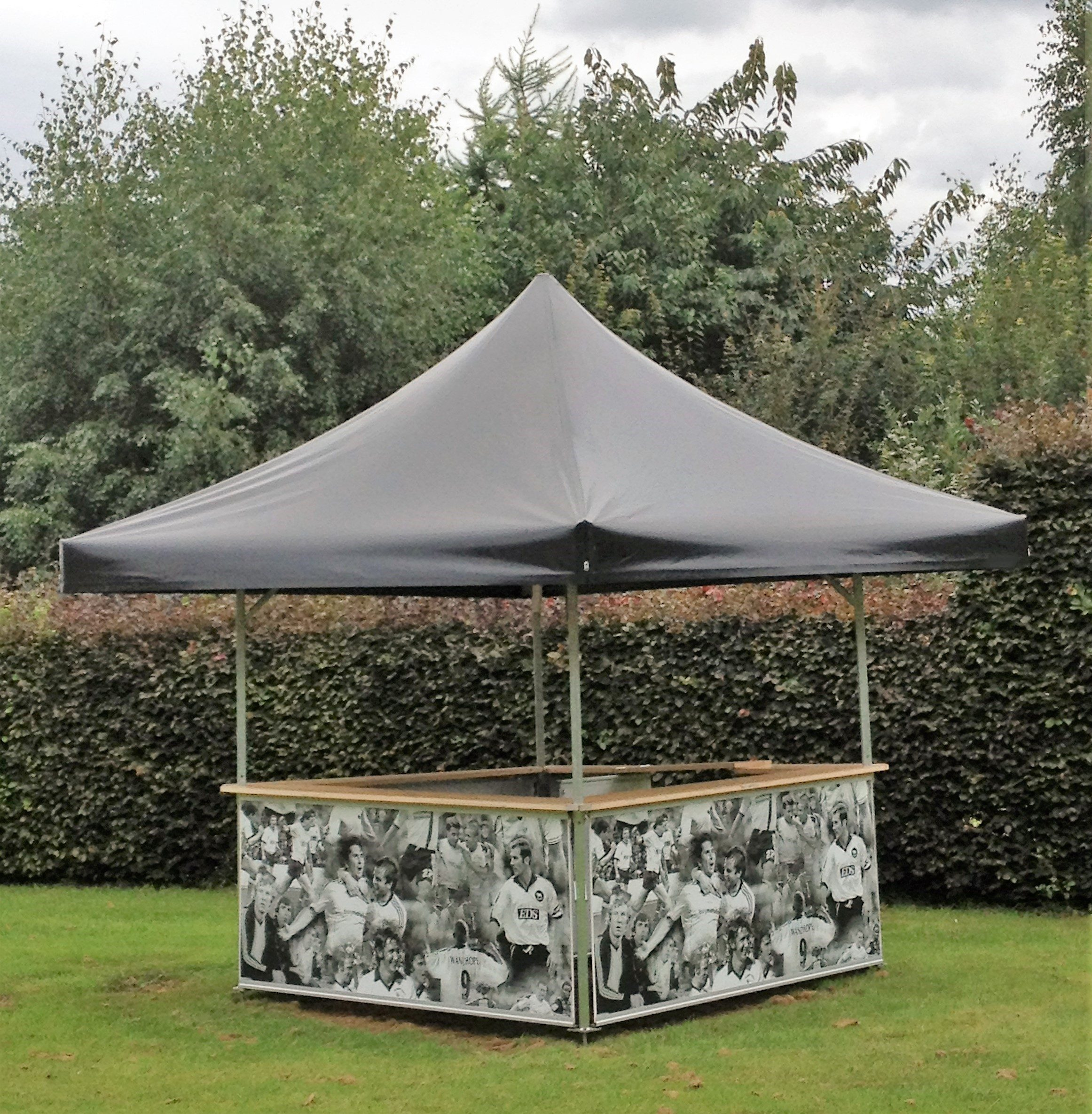 <p>Event, Mobile & Stadia Bars – Tents & Marquees – Square Pavilion</p> <p> </p> <p>Information stand with plain black roof and base panels branded with Derby County Football Club Legends</p>