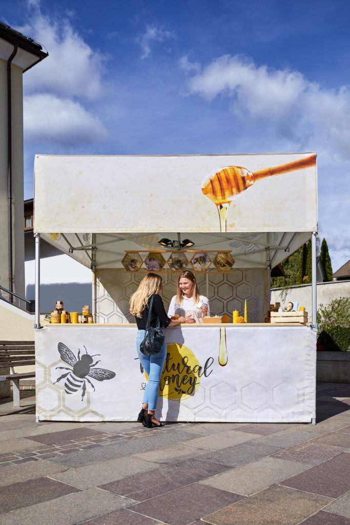 Square branded sampling stand displaying larger than average valance for advertising