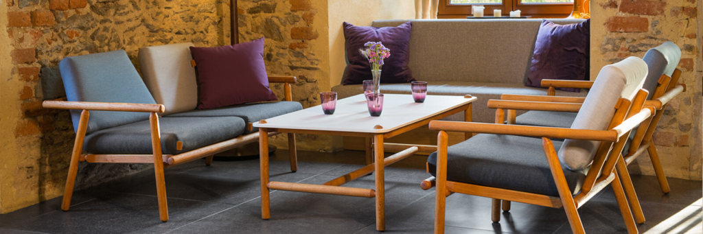 Outdoor Leisure Collection Hardwood Lounge Set displaying Armchairs, Table and Sofa in a coffee shop setting