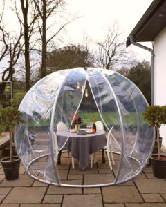 Dining Igloo All-Weather Dining Pod on an outdoor garden setting with table and chairs set